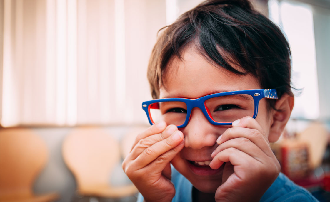 smiling kid putting on new glasses