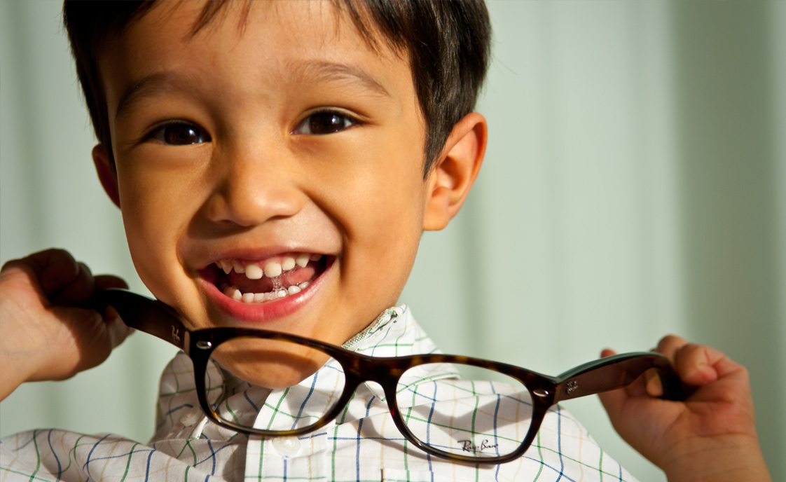 Young boy holding glasses
