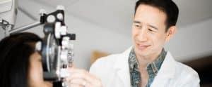 Honolulu eye clinic doctor Jeff Wong give eye exam to patient